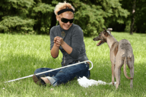 Picture of a young blind woman smiling while sitting in a green grassy yard with a cane and a dog