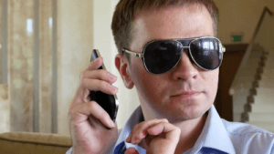 Picture of a blind man holding a cell phone listening to audio